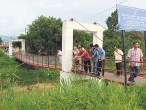 Penduduk kampung melihat keadaan Jambatan Gantung Kampung Baru Gurney yang didakwa condong selepas dibaiki pulih.