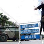 Anggota polis mengawasi kereta perisai pasukan tentera darat yang memasuki Jalan Tanjung Labian, di Felda Sahabat dalam usaha untuk mengetatkan lagi kawalan