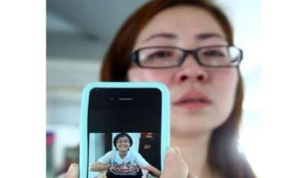 Ibu Ng Yuk Tim menunjukkan gambar anaknya yang hilang.