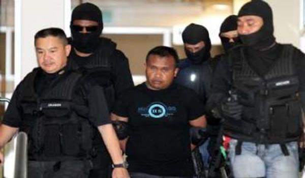 Suspek tiba di perkarangan mahkamah dengan kawalan ketat polis selepas diberkas di Kota Tinggi, Johor, awal pagi Ahad