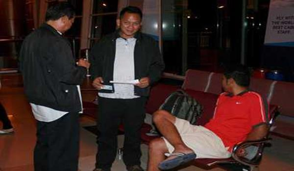 The suspect (seated) seen with officers at Kuching International Airport before he was brought to Kuala Lumpur.