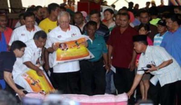 PERDANA Menteri, Datuk Seri Najib Tun Razak memeriksa barangan keperluan sebelum diagihkan kepada mangsa banjir di satu majlis di Chukai, Kemaman, Terengganu pada Ahad. Turut sama ialah Menteri Besar, Datuk Seri Ahmad Said dan Menteri Komunikasi dan Multimedia, Datuk Seri Ahmad Shabery Cheek.